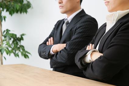 腕組みして考えるビジネスマン