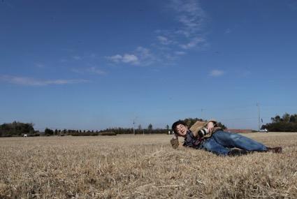 課税をめぐって揉める空き地に寝転ぶ筆者(2012年)