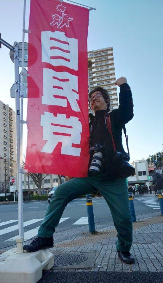 放置された幟と戯れる記者