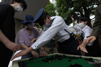 卓を囲む参加者と警官(らしき人)