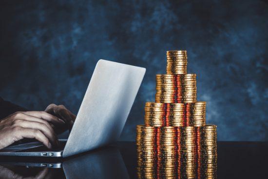 ノートパソコンとお金の山