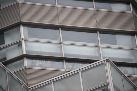 入管収容施設の窓からこちらを見る被収容者たち