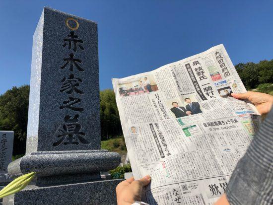 受賞決定を報じる新聞を掲げ墓前で報告する赤木雅子さん