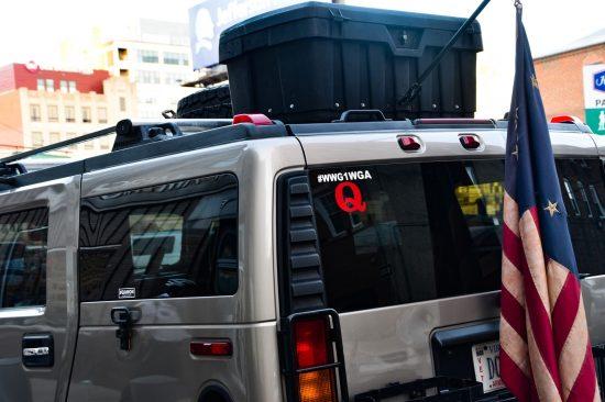「Q」のステッカーを貼る車