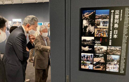 日本各地で起きた災害の写真にじっと見入る鳩山由紀夫・元首相