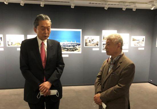 写真展のオープニングであいさつする鳩山氏。右は新藤健一氏